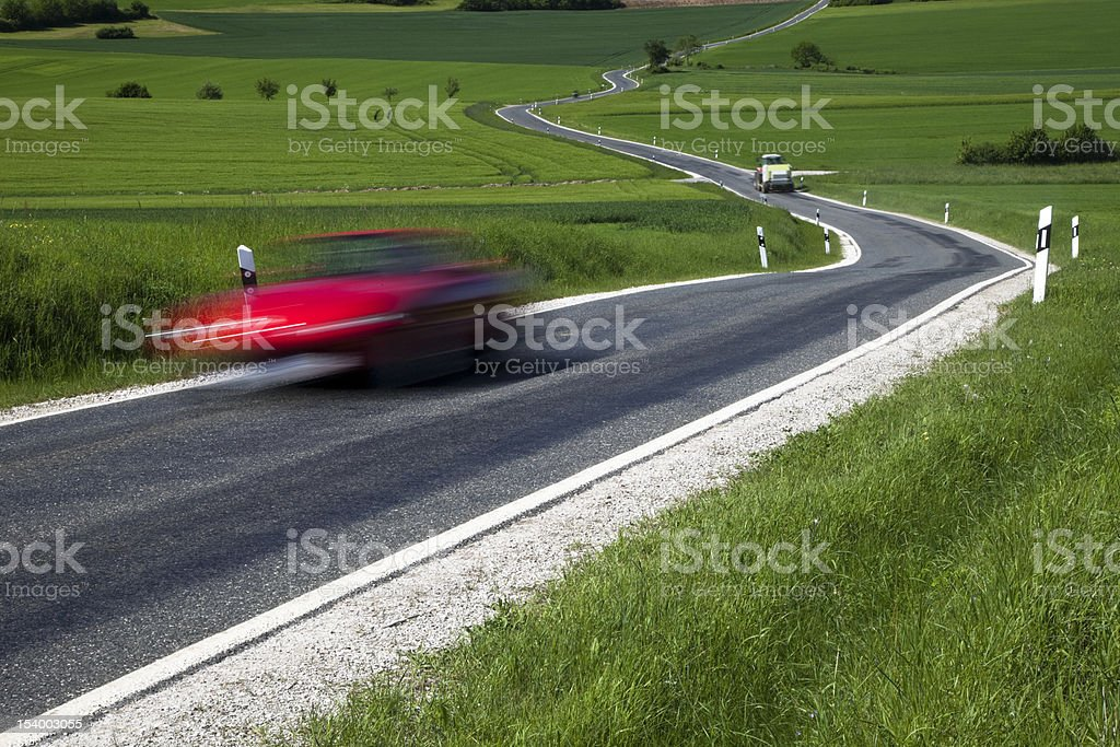 Red Car Driving on Winding Road in Spring Landscape royalty-free stock photo