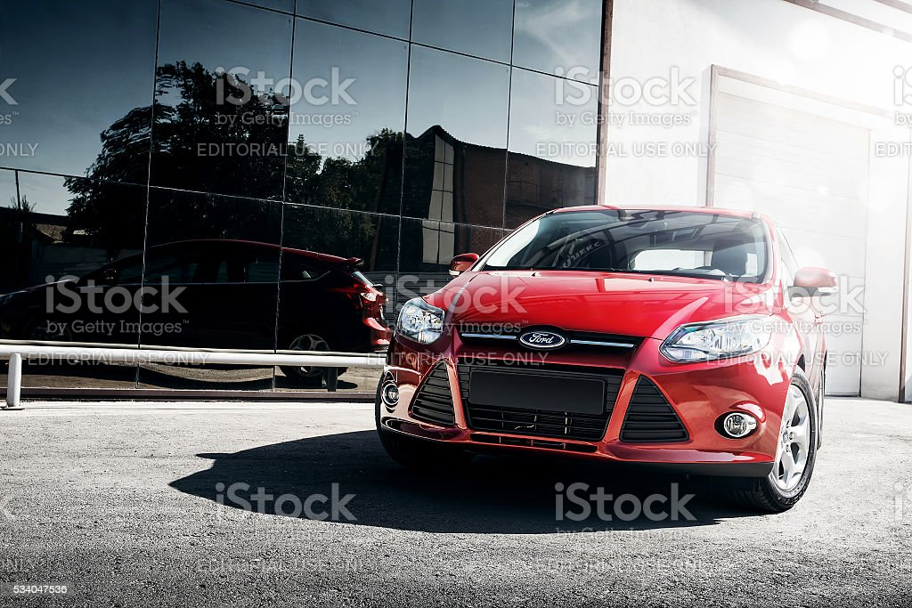 Red car Ford Focus III Sport standing near mirror build stock photo