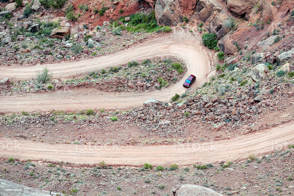 Red car on the road Long Canyon Rd,Moab,USA stock photo