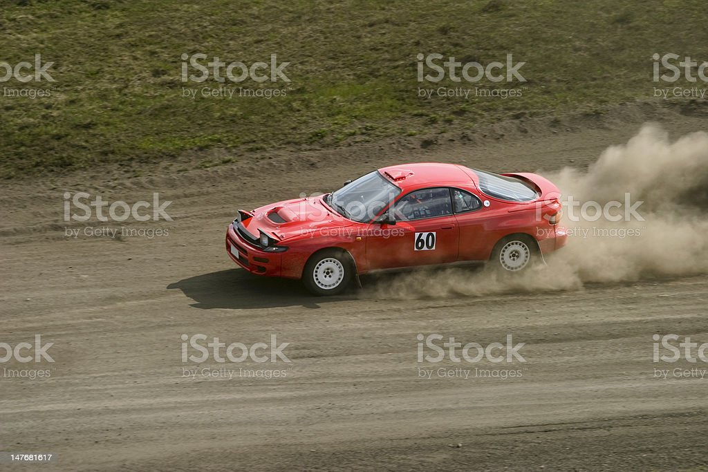 Red car racing down a dirt road stock photo
