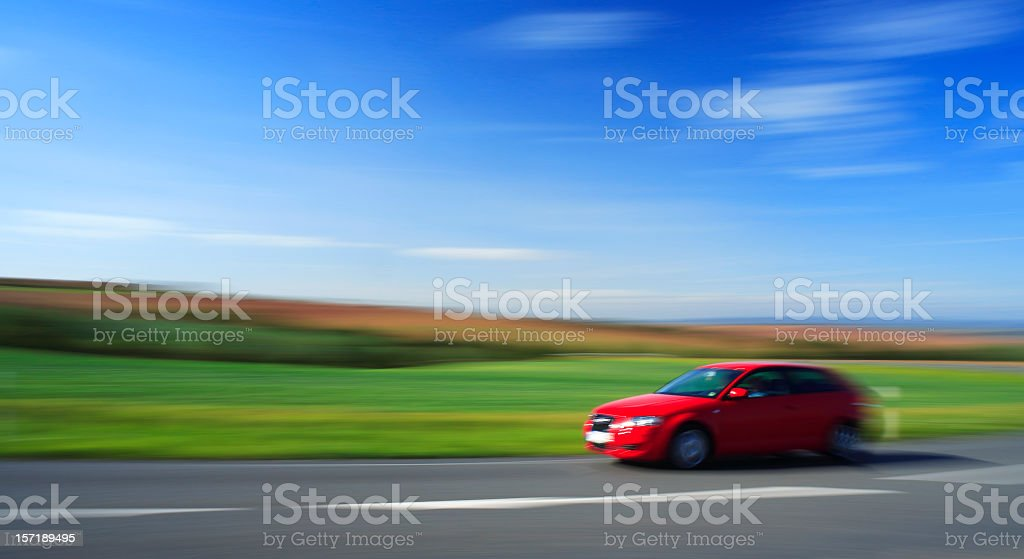 Red Car Speeding, Country Road Through Summer Landscape, intentionally blurred stock photo