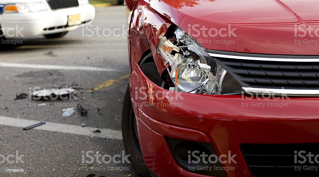 A red car with a damaged headlight after an accident stock photo