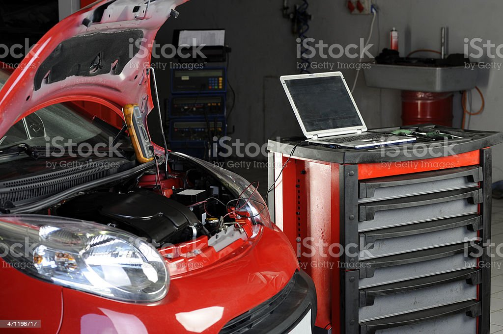 Red car with bonnet raised in mechanic's garage royalty-free stock photo