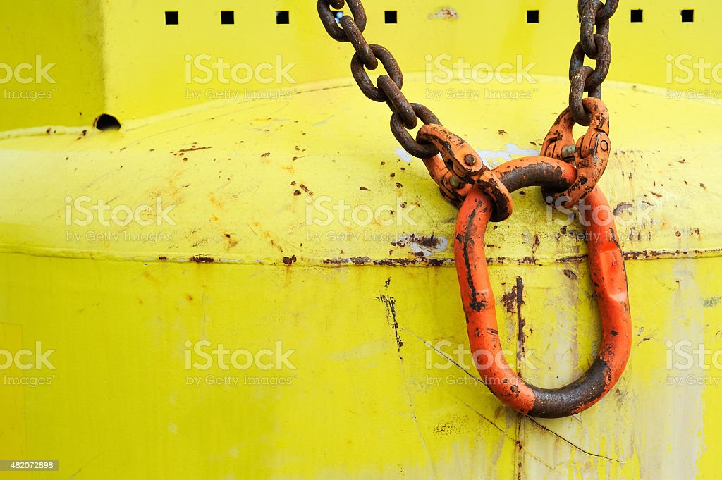 Red carabiner on yellow bottle stock photo