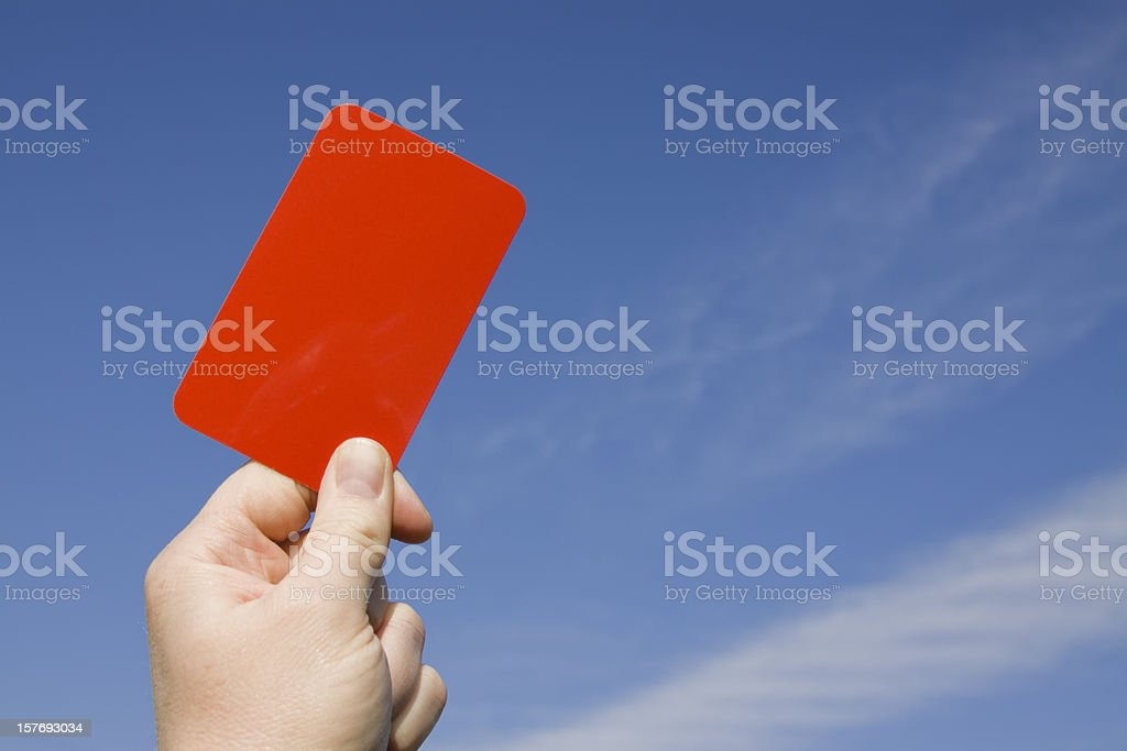 Red card held up against a blue sky. stock photo