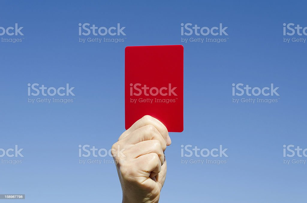 Red card in the hand against blue sky stock photo