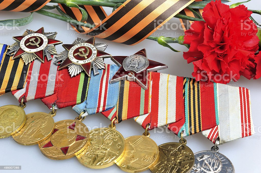 Red carnations with Saint George ribbon and medals on gray stock photo