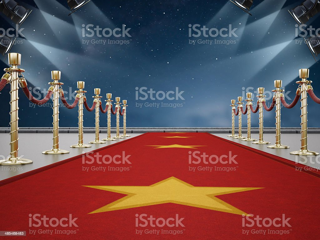 Red carpet and sky lit by spotlights stock photo
