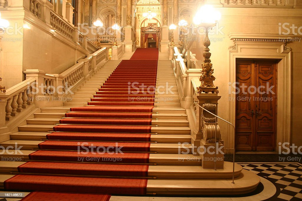 Red carpet cascading down a grand staircase stock photo