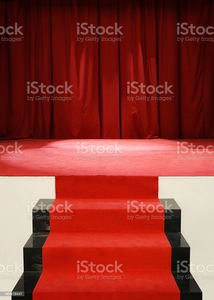 Red carpet on stairs to empty stage with curtain stock photo
