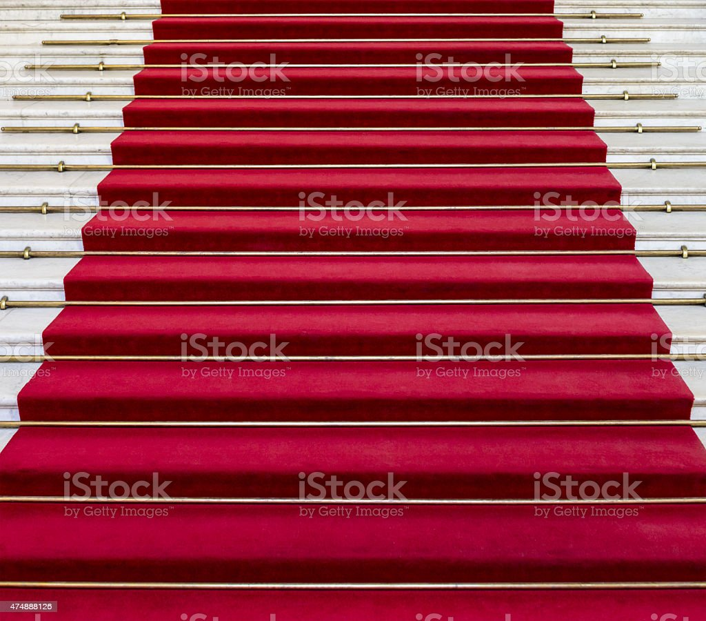 Red carpet on white marble stairs stock photo