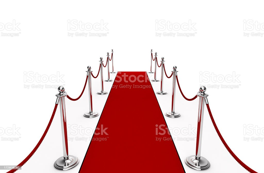 A red carpet with red rope and poles stock photo