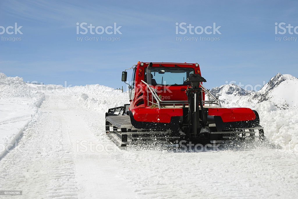 Red catterpillar tractor on snow slope against blue sky stock photo