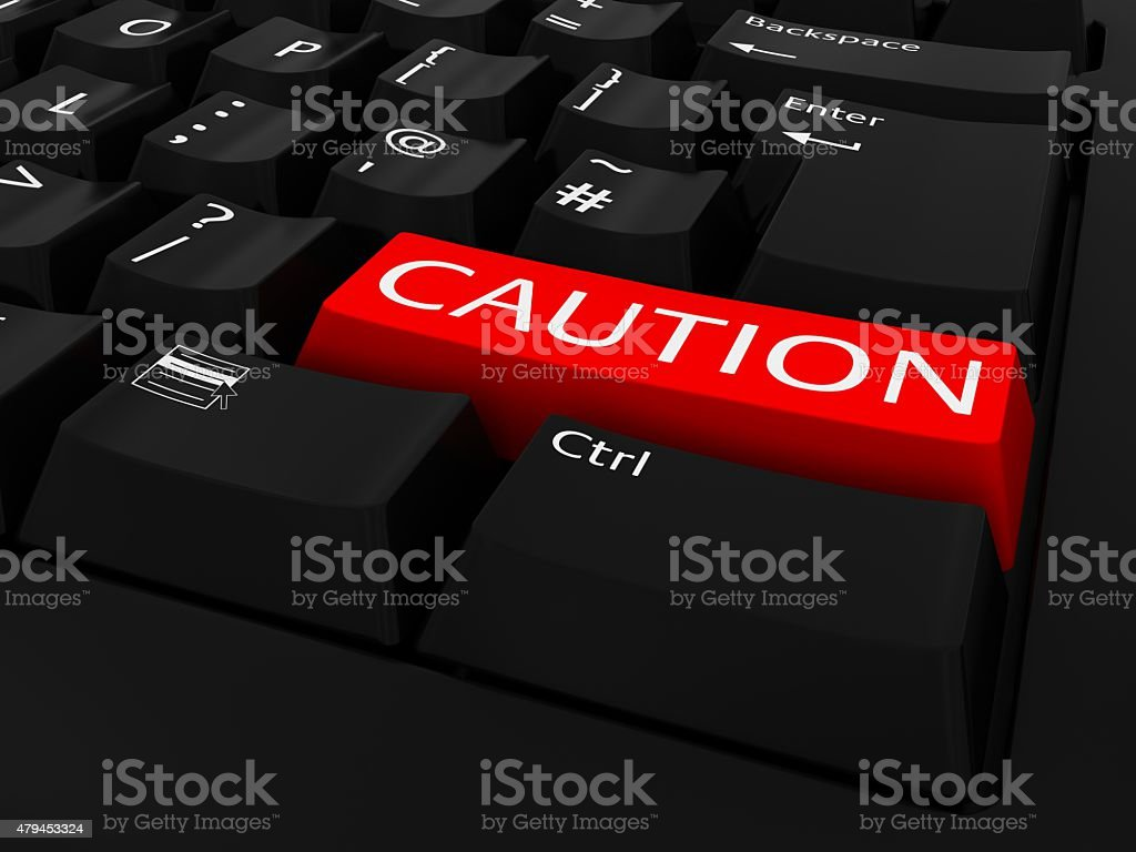 Red CAUTION Button on Black Keyboard stock photo