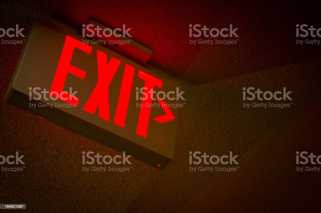 A red ceiling mounted EXIT sign stock photo