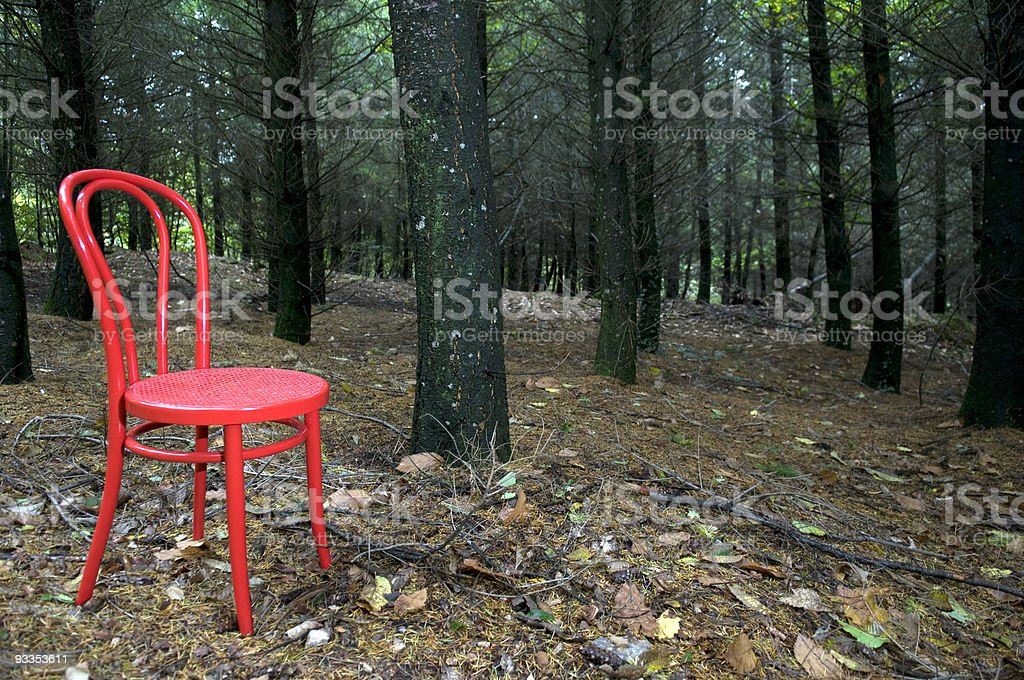Red chair in the woods stock photo