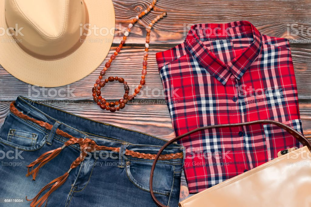 Red check shirt, jeans, leather hat, bag and belt stock photo