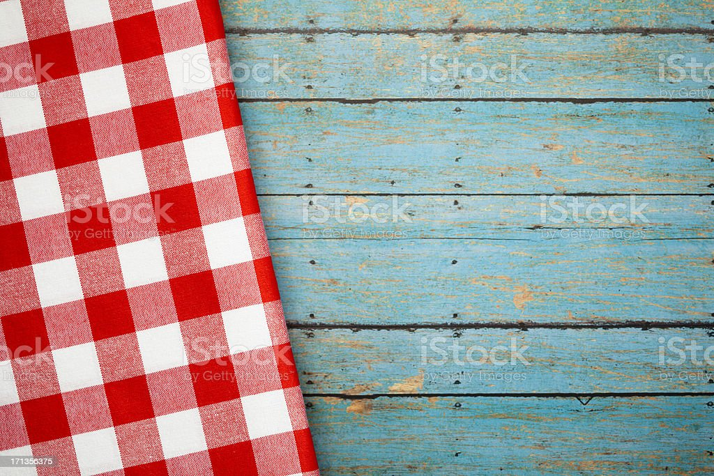 Red checked napkin on blue wooden picnic table stock photo