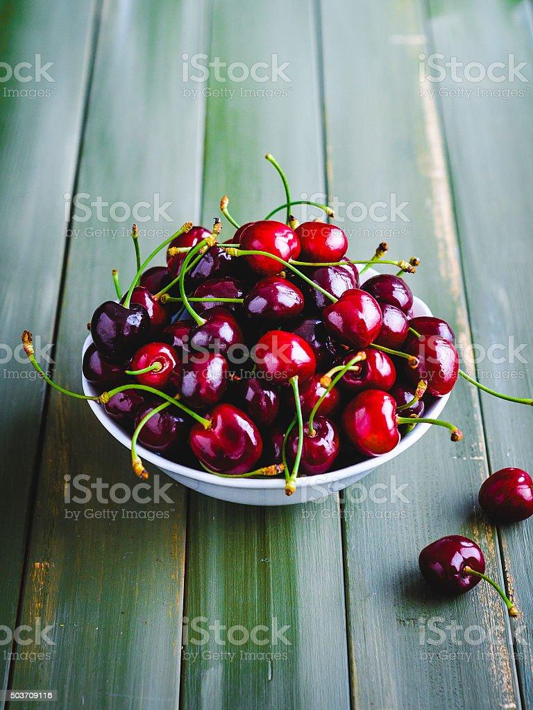 Red cherries in white bowl stock photo