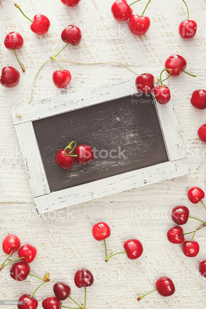 Red cherries on rustic table stock photo
