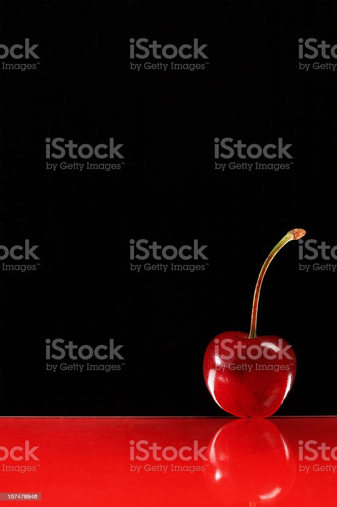 Red cherry on glass surface stock photo