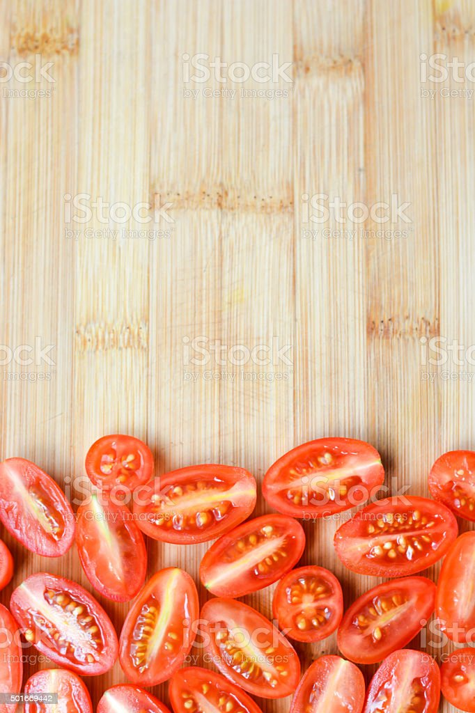 Red cherry tomatoes chopped on a wooden  cutting board stock photo