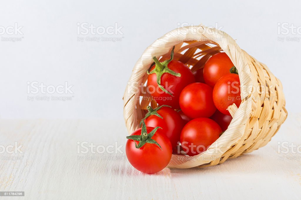 Red cherry tomatoes in a woven basket on a white background stock photo