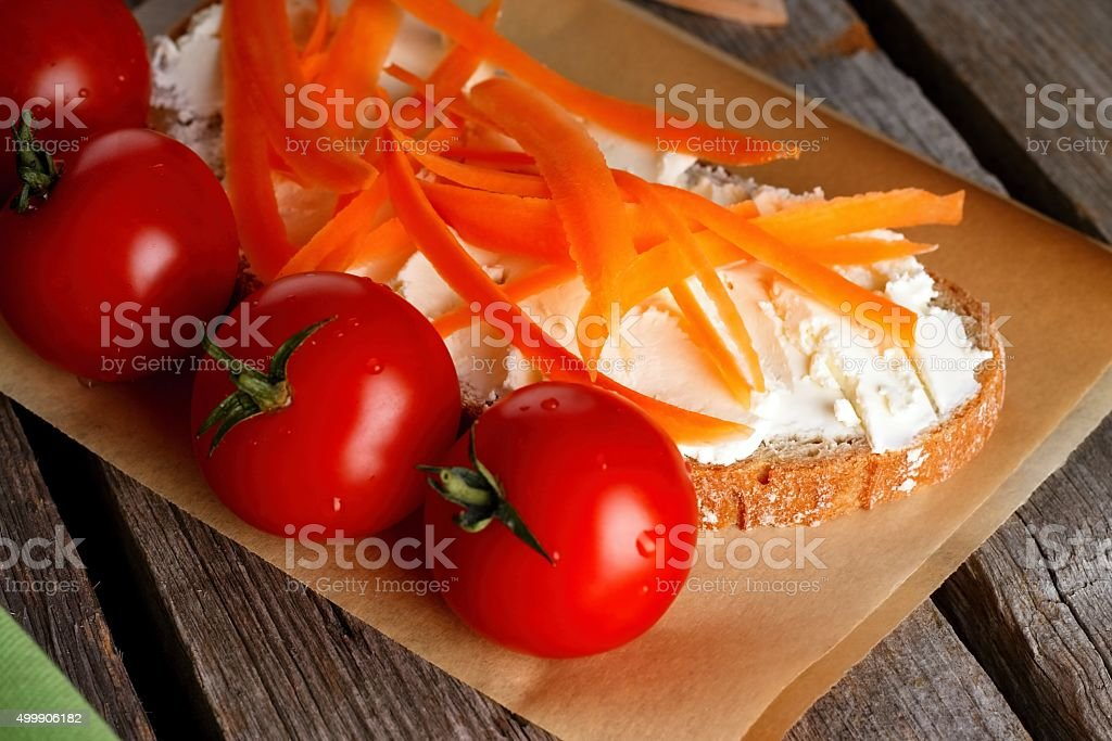 Red cherry tomatoes in front of bread with cottage stock photo