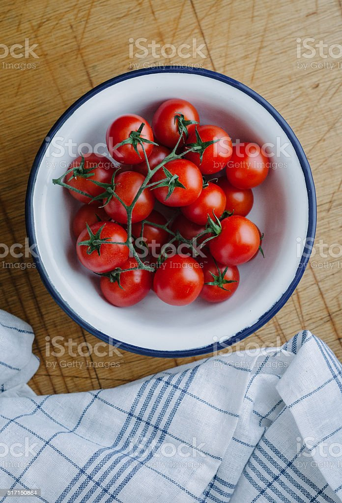 Red cherry tomatoes in white bowl stock photo