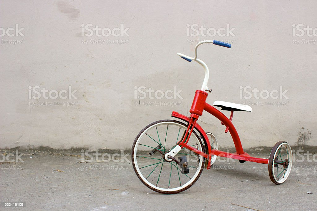 Red Children's Bicycle in front of a Grey Wall stock photo