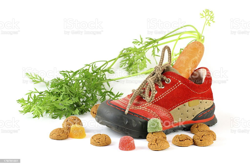 Red childrens shoe with carrot and pepernoten stock photo