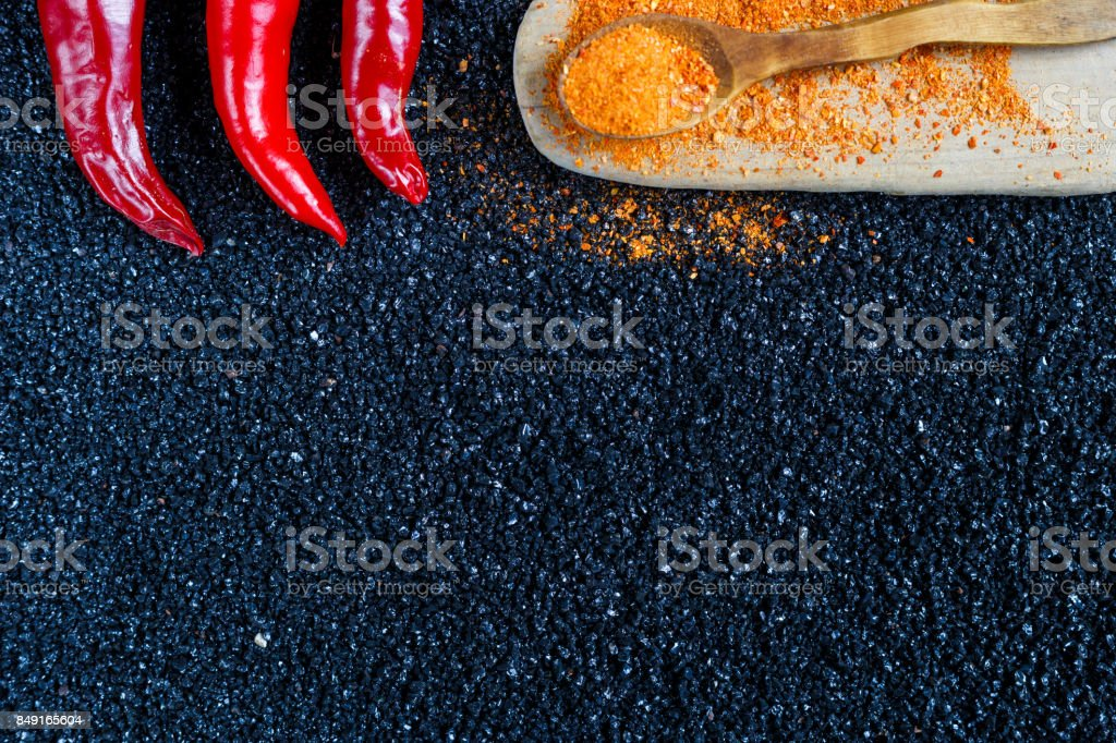 Red chili pepper, fresh and ground on darkly background, top view. Place for the text stock photo