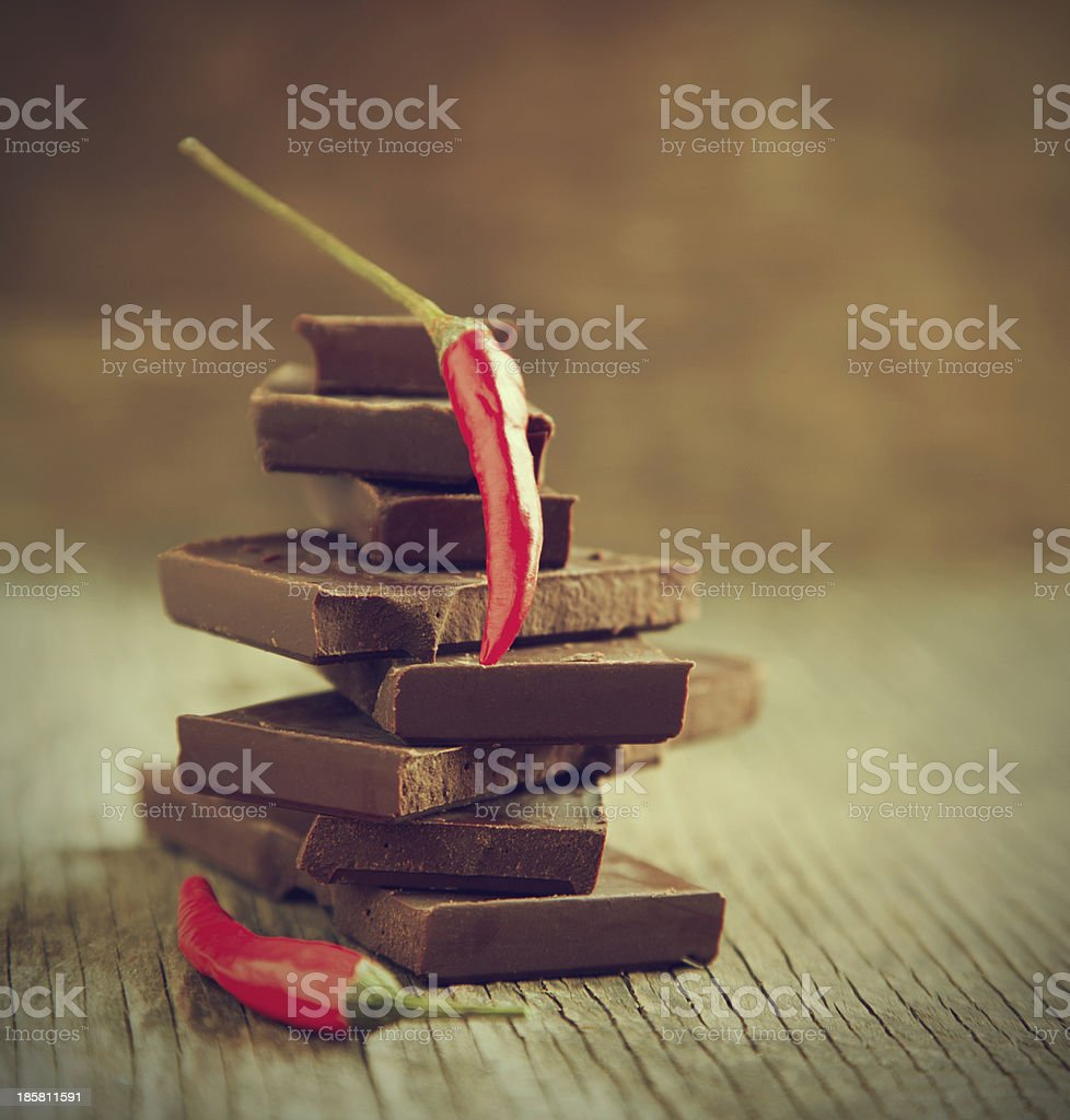 Red chili pepper on stack of dark chocolate pieces royalty-free stock photo