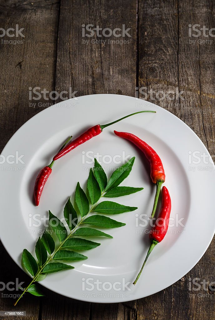 Red chilies and curry leaf on plate stock photo