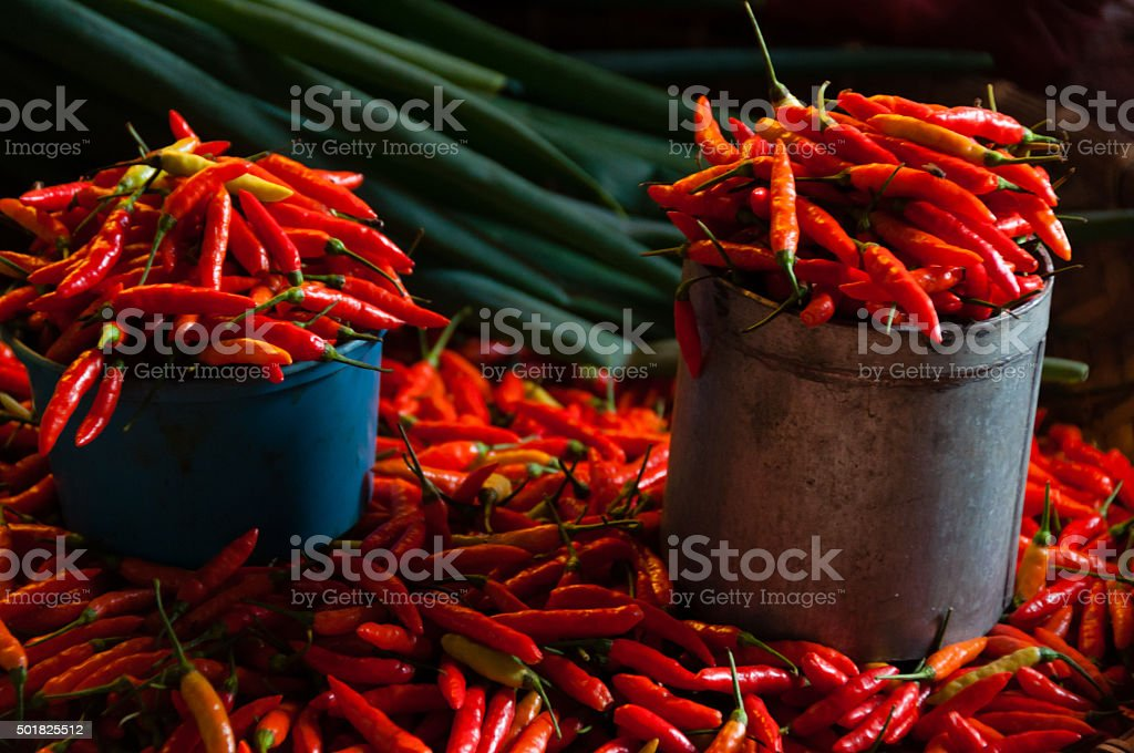 Red Chillies in bucket and laying around at local market stock photo