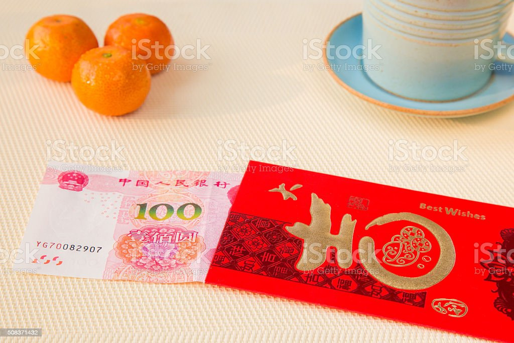 Red chinese envelope with money on a table stock photo