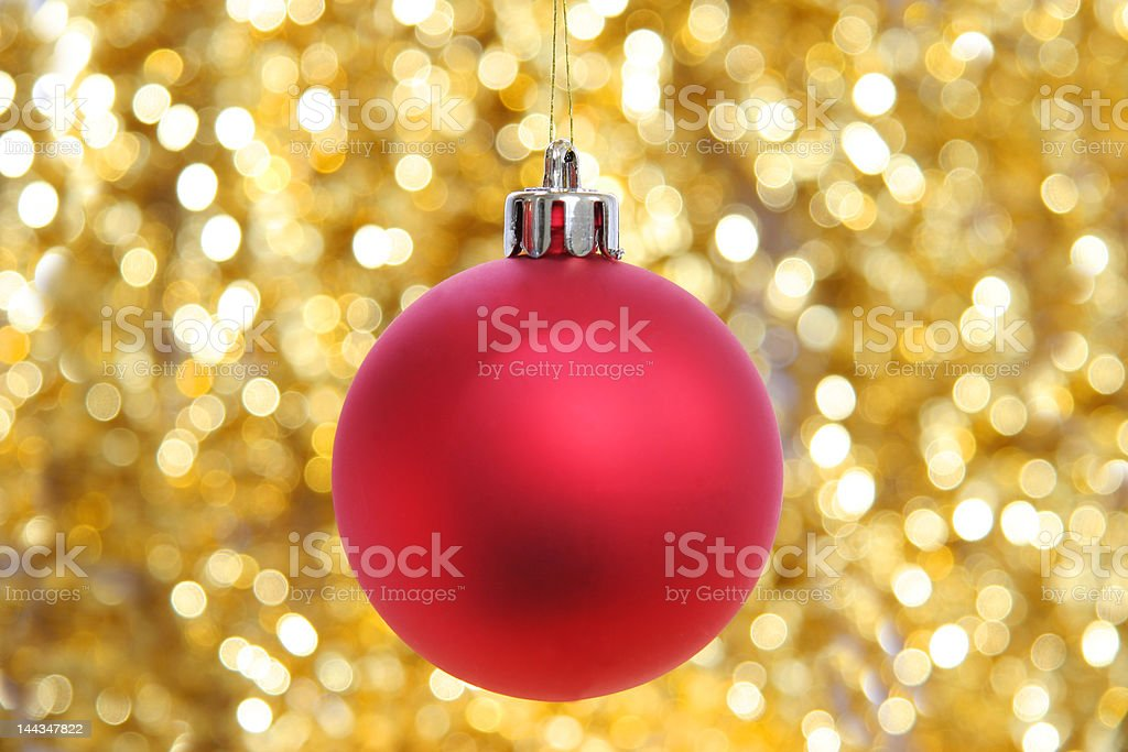 Red christmas ball against sparkling golden background royalty-free stock photo