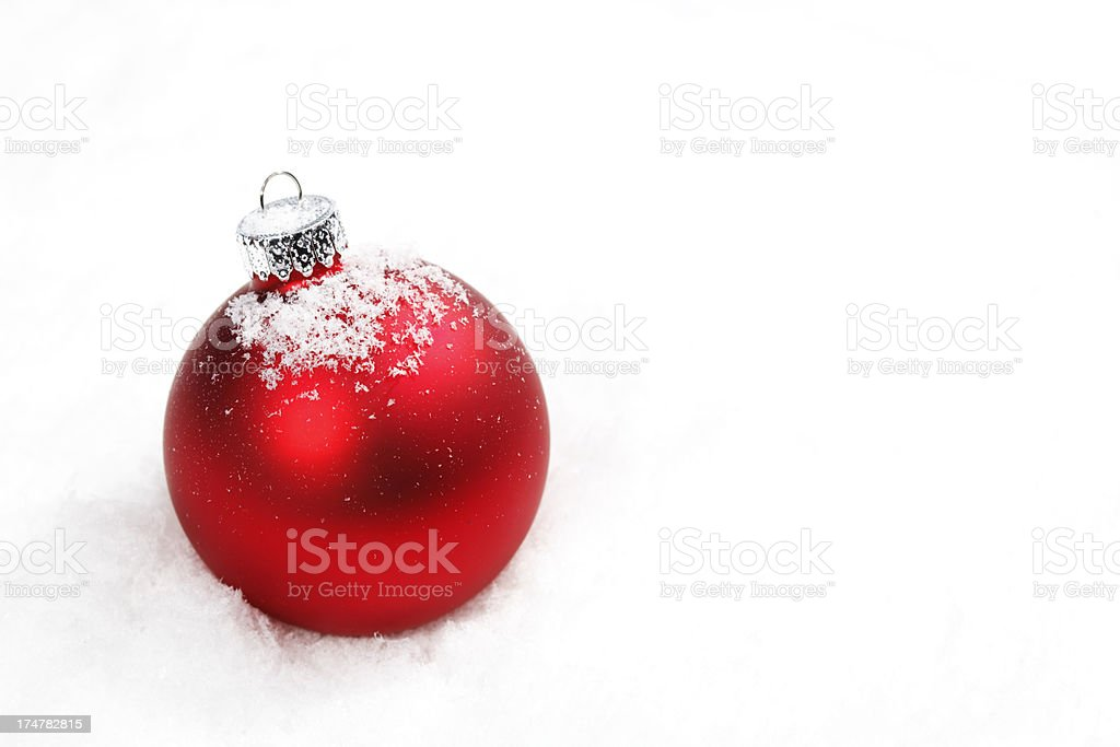 Red Christmas bauble with fake snow on white stock photo