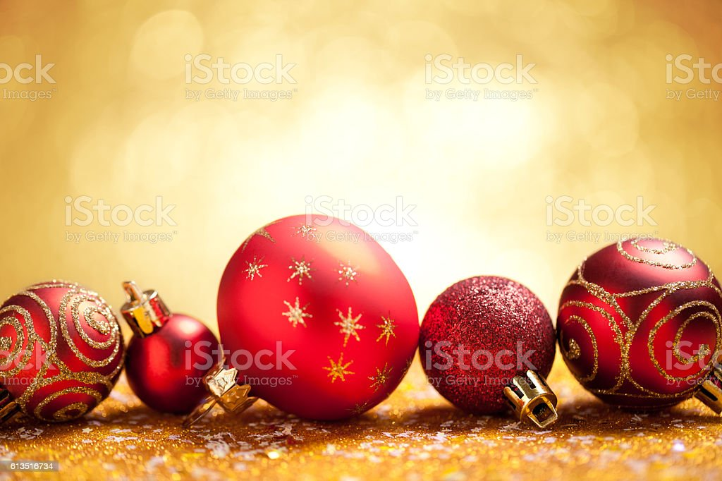 Red christmas baubles on gold glitter with yellow background stock photo