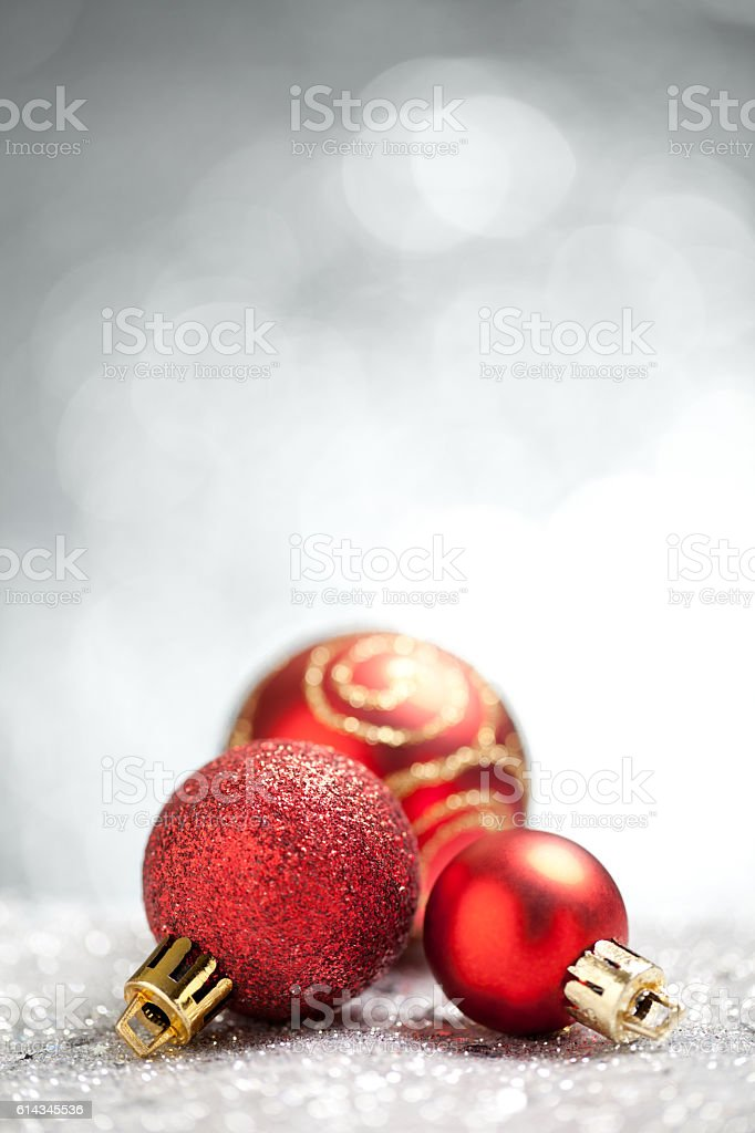 Red christmas baubles on silver glitter with grey background stock photo