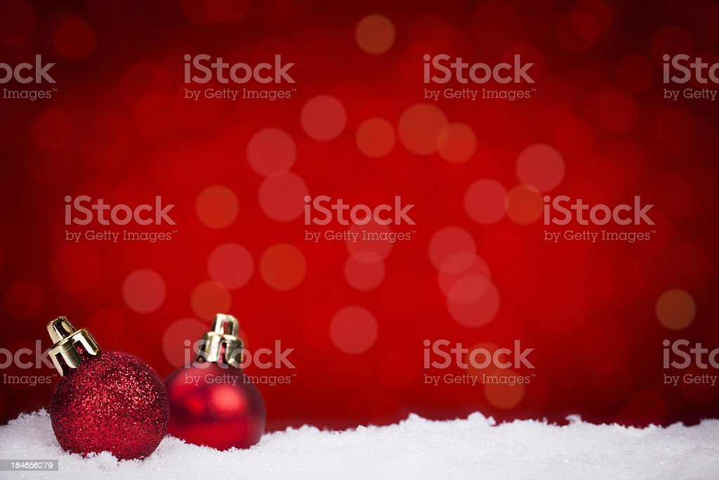 Red Christmas baubles on snow with a red background stock photo