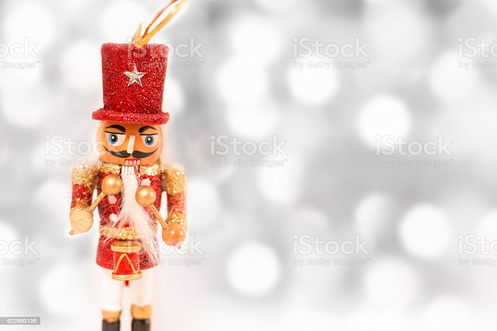 Red Christmas nutcracker ornament on white with lights. stock photo