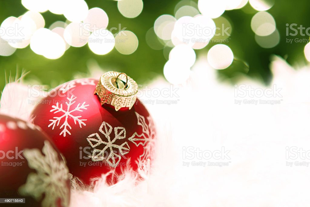 Red Christmas Ornaments On White Snow and Blur Christmas Lights stock photo