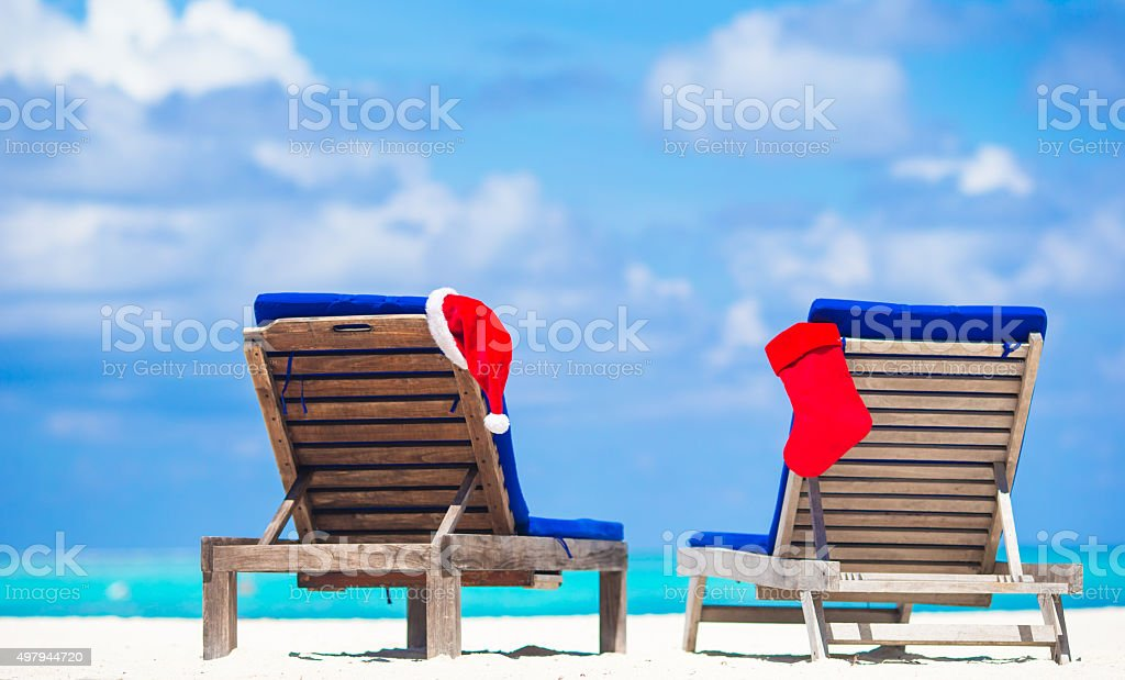 Red Christmas stocking and Santa Hat on chair at beach stock photo