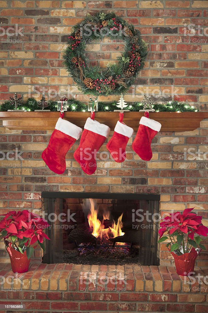 Red Christmas Stockings Fireplace Fire Wreath Poinsettias Mantel Decorations Hearth stock photo