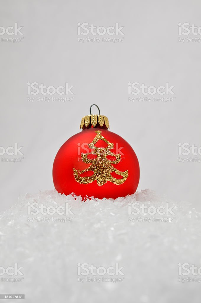 Red Christmas Tree Ball, golden ornament, laying in the snow royalty-free stock photo