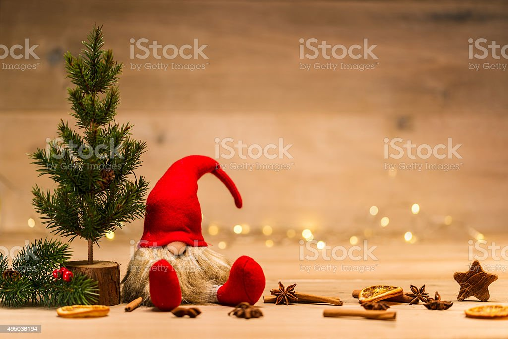 christmas dwarf sitting next to fir tree and x-mas decoration in...