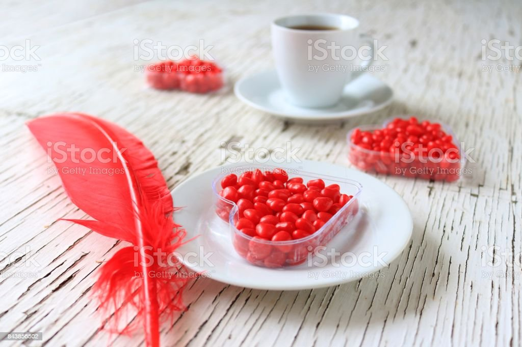 Red cinnamon heart candy displayed with coffee and a red feather on...