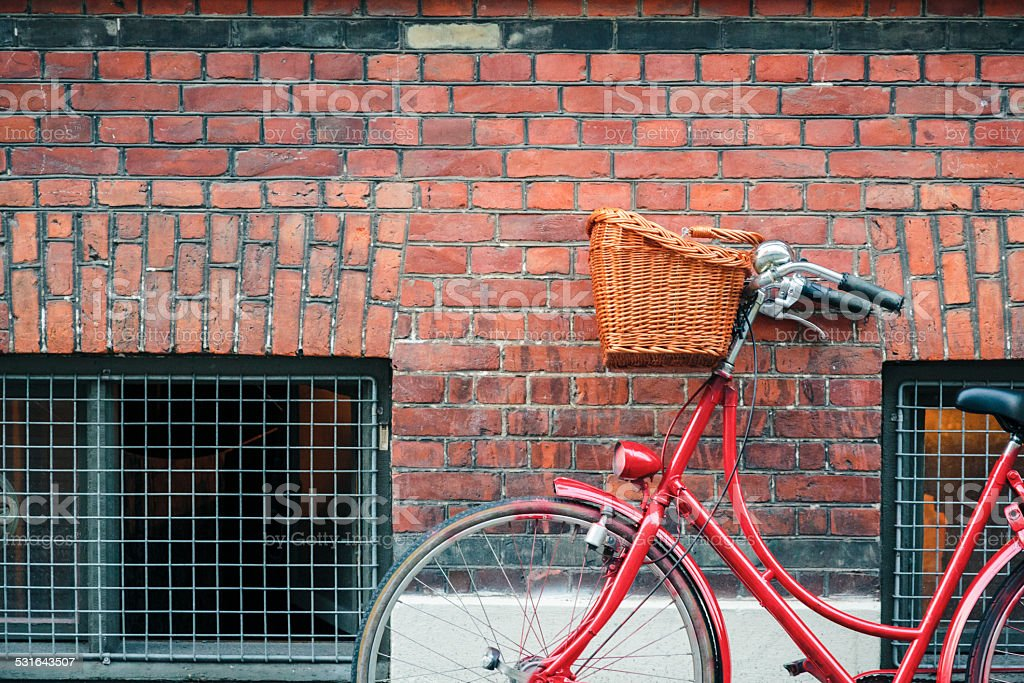 Red classic bicycle agains a brick wall in Copenhagen stock photo