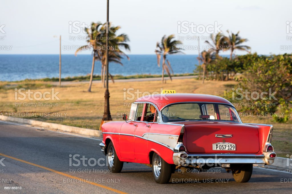 Red Classic Car driving along the coast in Cuba stock photo
